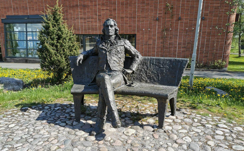 Veistos, jossa mies istuu puistonpenkillä