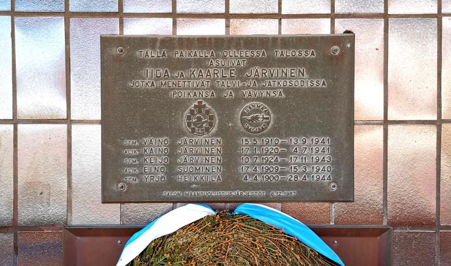 Muistolaatta, johon on kaiverrettu nimiä.