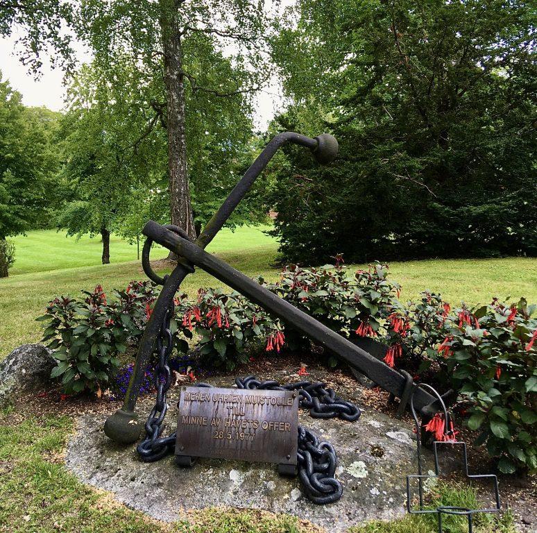 Muistomerkki, jossa on rautainen ankkuri. Kesä, kukkia, vihreitä lehtiä ja nurmikkoa. Ankkurin ympärillä punaisia kukkia.