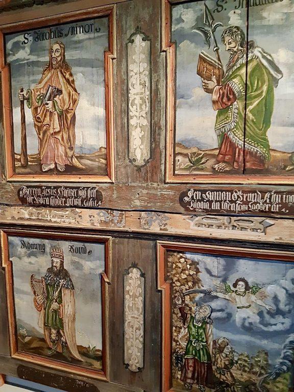 Vanhoja pinnasta kuluneita kristillisaiheisia maalauksia, jotk.a on maalattu puulle. Kuvien välissä lauseita Raamatusta.
