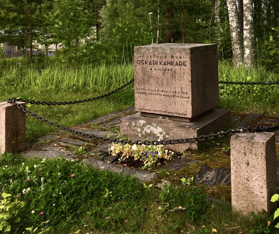 Kivinen muistomerkki, kesä, vihreä ympäristö.