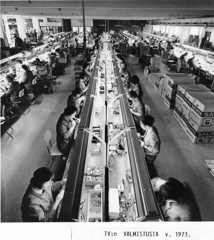 Mustavalkoinen kuva 1970-luvulta. Työntekijät kokoavat elektronisia laitteita suuressa tehdassalissa.