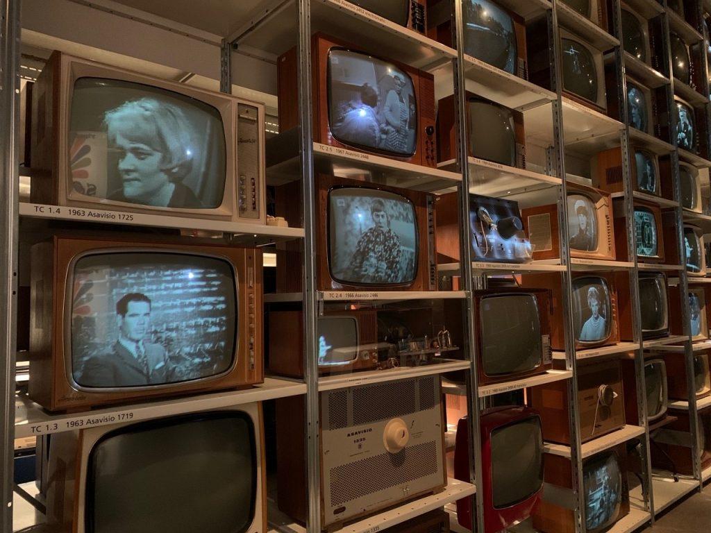 Hyllyssä paljon vanhoja tekevisioita, joissa kuvat vanhoista televisio-ohjelmista.