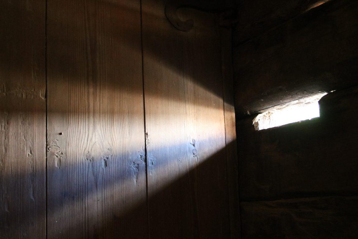 Sisällä huoneessa otettu kuva, jossa valo tulee huoneeseen pienestä seinällä olevasta luukusta
