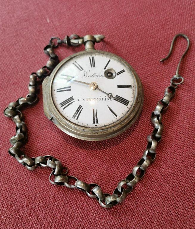 Vanha metallinen taskukello, jossa on roomalaiset numerot ja ketju.